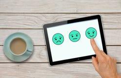 Kundendienst-Feedbackübersichtsfragebogen mit der Hand, die smiley wählt lizenzfreie stockfotos