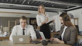 Kundendienstbetreiber, die Anrufe in besch?ftigtem Call-Center, Managerkontrolle ihre Arbeit nehmen stock footage