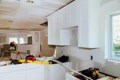 Kundenspezifische Küchenschränke in den verschiedenen Stadien der Installationsbasis für Insel in der Mitte lizenzfreie stockbilder