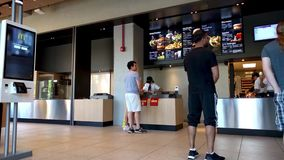 Kunder som väntar på matbeställningar i McDonald ` s Hamburgareuniversitet lager videofilmer