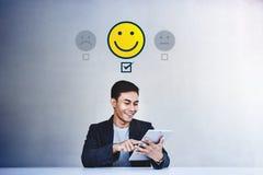 Kunderfarenhetsbegrepp Ung aff?rsman Giving hans positiva granskning i tillfredsst?llelseonline-granskning Lycklig klient arkivfoto