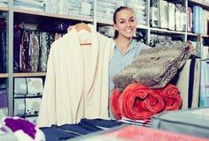 Kundin, die mehrfache Einzelteile im Textilspeicher kauft Stockfotos