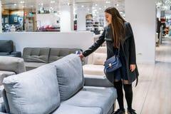 Kundkvinna som köper nytt möblemang - soffa eller soffa i ett lager arkivbild
