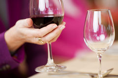 Kunds exponeringsglas för vin för hand hållande på restaurangtabellen Royaltyfri Foto