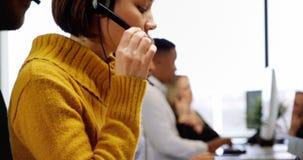 Kundtjänstledare som talar på hörlurar med mikrofon på skrivbordet 4k lager videofilmer