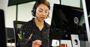 Kundtjänstledare som talar på hörlurar med mikrofon på skrivbordet 4k stock video