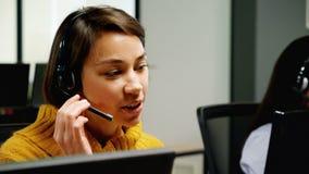 Kundtjänstledare som talar på hörlurar med mikrofon på skrivbordet arkivfilmer
