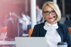 Kundtjänstrepresentant på arbete Härlig ung kvinna i hörlurar med mikrofon som arbetar på datoren Arkivbilder