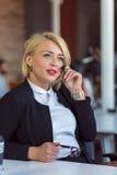 Kundtjänstrepresentant på arbete Härlig ung kvinna i hörlurar med mikrofon som arbetar på datoren Arkivbild