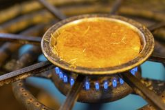 Kunefe is cooked on burning gas stove hob blue flames in Hatay,. Turkey stock image