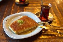 Kunefe turco del dessert con la polvere ed il tè del pistacchio fotografia stock libera da diritti
