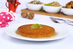 Kunefe / Turkish Traditional Dessert. Turkish dessert kunefe with nuts served in plate stock image