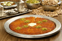 Kunefe / Turkish Traditional Dessert. Turkish dessert kunefe with Pistachio served in classical aluminum plate stock photo