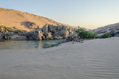 Kunene River in front of towering ancient Namib Desert sand dunes of Namibia and Angola Royalty Free Stock Photos