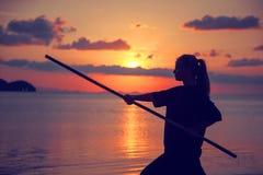 Kung-fu facente biondo della giovane bella donna della ragazza con il bastone di bambù sulla spiaggia al tramonto, lotta fotografie stock