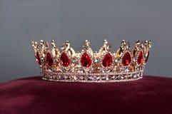 Kunglig krona med röda ädelstenar Rubin granatrött Symbol av makt och myndighet Arkivfoto