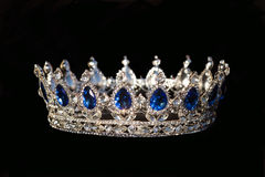 Kunglig krona med safir på svart bakgrund arkivfoto
