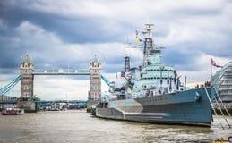 Kunglig marinkryssare HMS Belfast som förtöjas i Themsen med tornbron i bakgrund, London, England Royaltyfri Fotografi