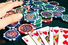 Kunglig personexponeringsseger i poker och kvinnliga händer som griper banken Arkivfoton