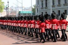 Kungliga Guards marscherar in mot den Buckingham slotten Arkivbild