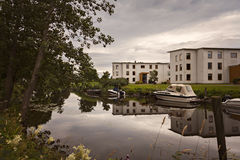 Kungsbacka riverside view. KUNGSBACKA, SWEDEN - July 21, 2017. Boats and apartment blocks by the river Royalty Free Stock Photography