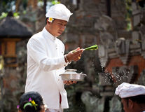 Kuningan Festival in Bali. UBUD, BALI, INDONESIA- JULY 16: Unidentified villagers receive a blessing at the Balinese Temple during the Kuningan Festival  on July Stock Photos