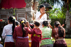 Kuningan Festival in Bali. UBUD, BALI, INDONESIA- JULY 16: Unidentified villagers receive a blessing at the Balinese Temple during the Kuningan Festival on July Royalty Free Stock Photos