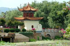 Kunming, China: Daguan Park Passing Gate. The elegant Passing Gate pavilion with tiled flying eave roofs leads to a small bridge lined with colourful Stock Photo