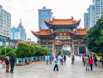 KUNMING KINA - SEPTEMBER 9, 2012: Kunming valvgång Port för traditionell kines och moderna byggnader av centret, Kunming arkivfoton
