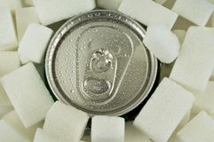 Kunna av sodavatten som omges av sockerkuber arkivbild