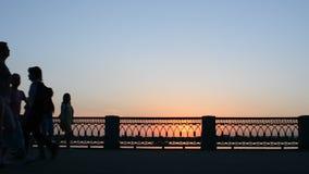 26 kunnen 2016, Rusland, Samara - stadsdijk De mensen lopen, berijden, fiets langs de rivier Donkere silhouetten bij zonsondergan stock footage