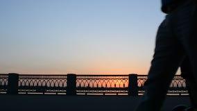 26 kunnen 2016, Rusland, Samara - stadsdijk De mensen lopen, berijden, fiets langs de rivier Donkere silhouetten bij zonsondergan stock videobeelden
