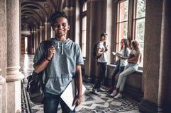 Kunskap bemyndigar dig Stiligt ungt studentanseende på korridoren av universitetsområdet och att le royaltyfri bild