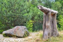 Kunst in aard - houten dier naast een steen Stock Fotografie