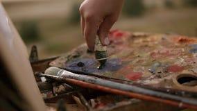 Kunst, Kreativität und Leutekonzept Abschluss oben des Künstlers verdrängt Farbe vom Rohr auf der Palette draußen stock video