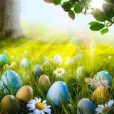 Kunst verzierte Ostereier im Gras mit Gänseblümchen Stockbilder