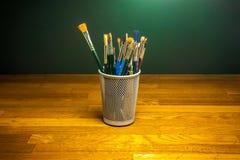 Kunstakademiebürsten auf hölzernem Studioschreibtisch Lizenzfreie Stockfotografie