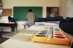 Kunstakademieklassenzimmer, das Aquarellfarbenkasten und -tafel anzeigt lizenzfreies stockfoto