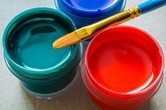 Kunstbürsten und wenige Gläser mit Acrylfarbe Lizenzfreie Stockfotos