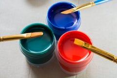 Kunstbürsten und wenige Gläser mit Acrylfarbe Stockfotos
