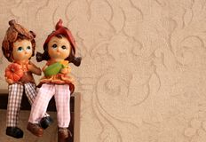 Kunstbeeldhouwwerk van jongen en meisje in liefdezitting samen met gekruiste benen stock afbeeldingen
