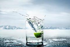 Kunstbild der Zitrone geworfen zum Glas des Wassers Lizenzfreie Stockfotos