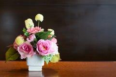 Kunstbloemenreeksen in witte vaas, achtergrondbord Royalty-vrije Stock Afbeeldingen