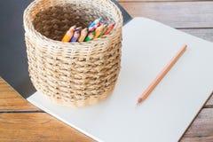 Kunstdruckpapierbuch und viele verschiedenen farbigen Bleistifte Lizenzfreie Stockfotos