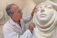 Kunstenaar aan het werk in studio op een beeldhouwwerk van gezicht Stock Afbeelding