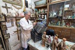 Kunstenaar in de kunststudio op het werk aangaande een metaalbeeldhouwwerk van een grote oude lamp Royalty-vrije Stock Afbeeldingen