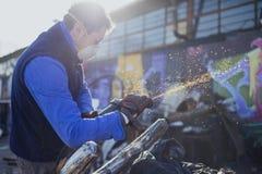 Kunstenaar die en zijn zilveren Boombeeldhouwwerk in de zonsondergang buiten in de voorzijde van zijn Workshop malen oppoetsen ma Stock Afbeeldingen