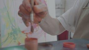 Kunstenaar die oranje verf van een fles met zijn borstel nemen stock videobeelden