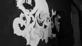 Kunstenaar die witte grafiti met schedel op de zwarte muur schilderen stock video