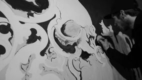 Kunstenaar die witte grafiti met schedel op de zwarte muur schilderen stock videobeelden